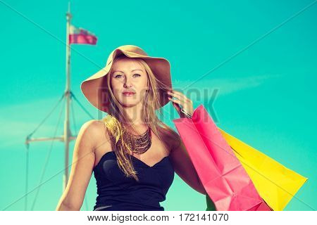 Spending money buying things concept. Portrait of attractive elegant woman holding shopping bags wearing glamorous outfit with clear blue sky and polish flag in background