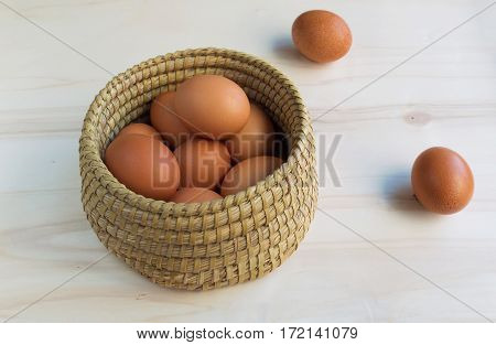 Fresh organic eggs in a basket placed on a wooden surface
