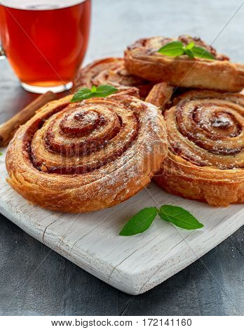 Freshly Baked Traditional Sweet Cinnamon Rolls, Swirl on white wooden board with hot black Tea and mint.
