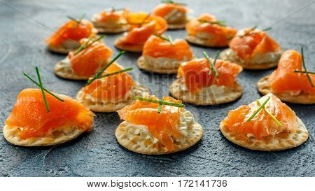 Smoked Salmon and soft chees canapes appetizers with chives on stone table.