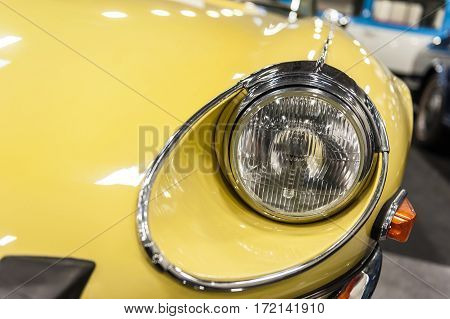 Closeup on headlight of a yellow car in the sunlight