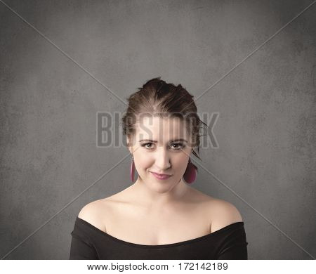 A pretty young teenage girl standing in front of a grey clear empty urban wall background concept while making funny faces.
