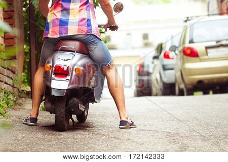 Man Riding Old Retro Scooter In A City Street. Close Up