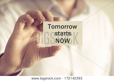 Businessman Holding Tomorrow Starts Now Message Card