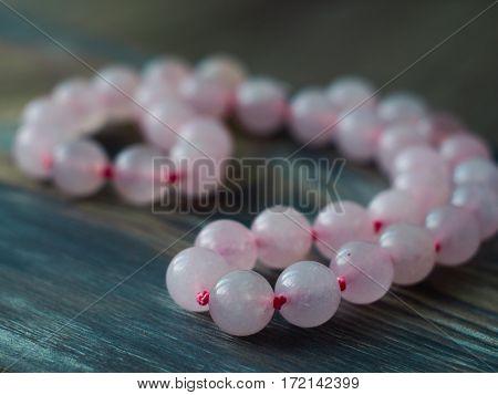 Beautiful Pink quartz bracelet on wooden table