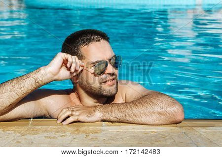 Happy attractive young man in sunglasses resting relaxed on edge of swimming pool. Close up portrait of a handsome and happy young man relaxing resting on his hands at the side of a sun bathed swimming pool.