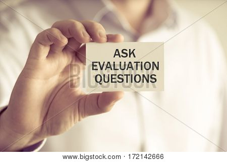 Businessman Holding Ask Evaluation Questions Card