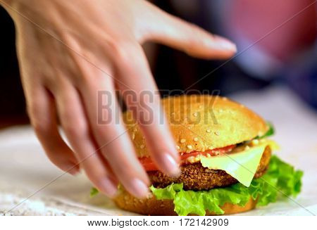 Hamburger fast food with ham on wooden board . Group of hamburger. Close up of human hand take off table cheeseburger.