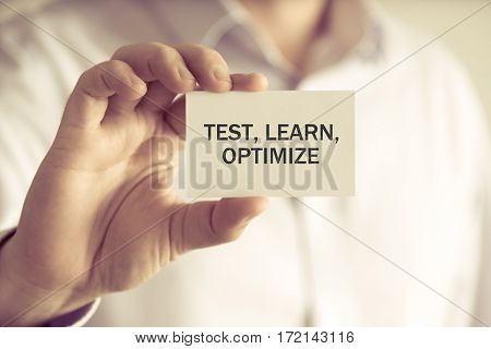 Businessman Holding Test, Learn, Optimize Message Card
