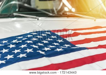 USA flag on the hood of a white car with sunlight