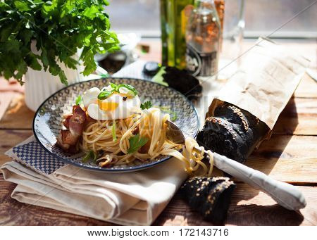 Pasta Carbonara On Plate With Bacon And Egg Plows On Dark Wood Background