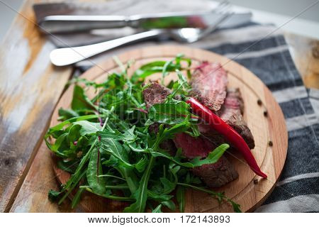The fragrant cut meat with greens and arugula on a wooden plate against a table in rustic style