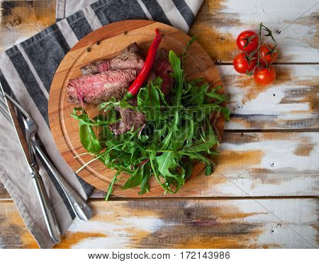 Tasty Cut Meat Steak With Greens And Arugula On A Wooden Plate Against A Table In Rustic Style