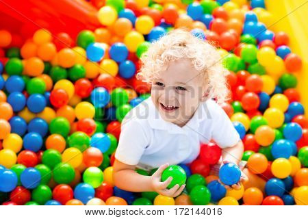 Happy laughing boy having fun in ball pit on birthday party in kids amusement park and indoor play center. Child playing with colorful balls in playground ball pool. Activity toys for little kid.