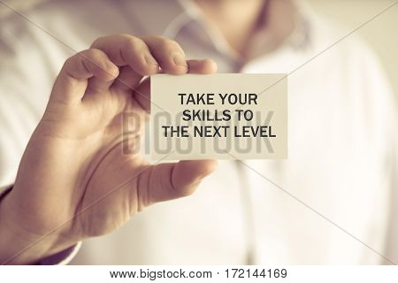Businessman Holding Take Your Skills To The Next Level Message Card