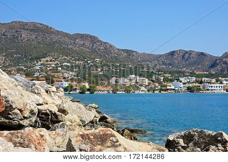 MAKRIGIALOS, CRETE - SEPTEMBER 18, 2016 - View of the beach and town with large rocks in the foreground Makrigialos Crete Greece Europe, September 18, 2016.