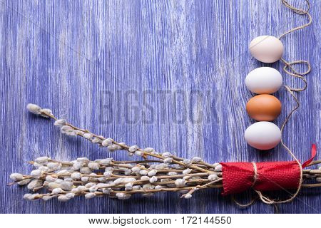 Willow twigs blooming and Easter eggs on a blue wooden table