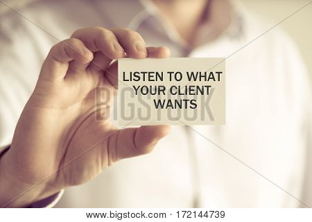 Businessman Holding Listen To What Your Client Wants Message Card