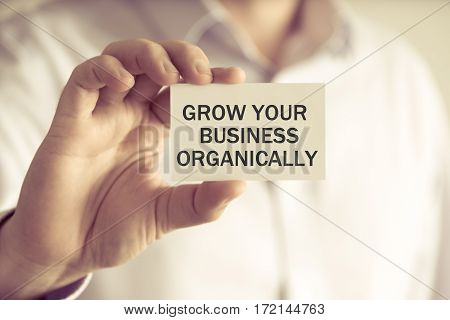 Businessman Holding Grow Your Business Organically Message Card