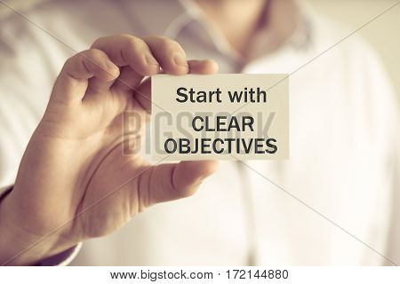 Businessman Holding Start With Clear Objectives Message Card