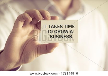 Businessman Holding It Takes Time To Grow A Business Message Card