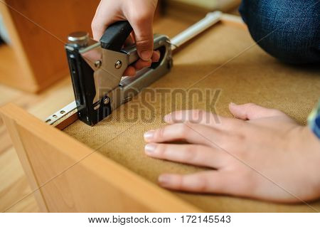 Worker repairing furniture with industrial construction stapler