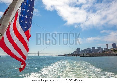 San Francisco Financial District skyline and Oakland Bridge on sunny day, California, United States. Sea views from the ship to Alcatraz island with American flag waving. Freedom and travel concept.
