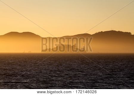 Beautiful view of famous Alcatraz Island illuminated in majestic golden evening light at sunset in summer San Francisco Bay, California, USA