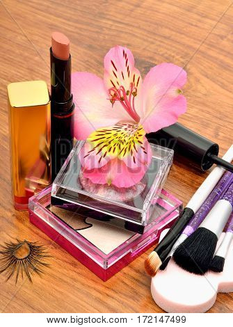 Cosmetics and orchid on wooden background closeup