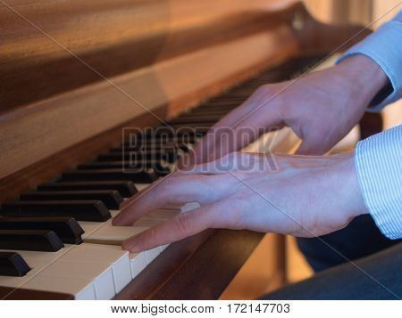 Side view of musician hands playing classic piano.