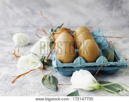 raw eggs in a carton for eggs with white flowers on a marble white table, ready for painting Easter, the space under the text, selective focus