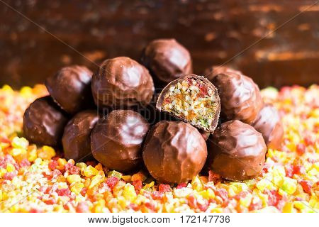 Candied roasted hazelnuts and peanuts with dried apricot, dried cherry, candied pineapple fruit and honey in dark chocolate glaze, selective focus