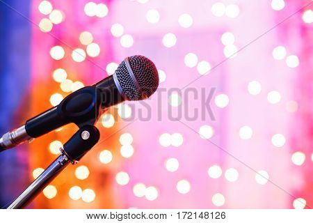 Close up of microphone in concert hall with blurred lights at background.