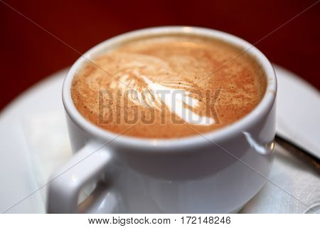Cup of cappuccino on saucer in cafe