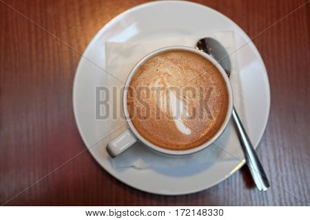 Сup of coffee on wooden table in cafe