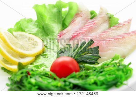 Sashimi perch, vegetables, lettuce, tomato, perch on a white background