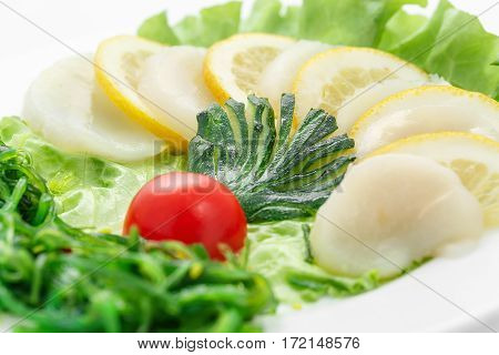 Sashimi of scallops, vegetables, lettuce, tomato, scallop over white background