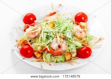 Caesar salad shrimps, iceberg lettuce, parmesan cheese, Caesar sauce, shrimp, cherry tomatoes on a white plate on a white background