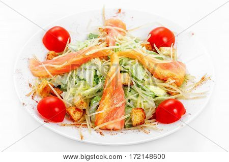 Caesar salad with salmon, iceberg lettuce, parmesan cheese, Caesar sauce, salmon, cherry tomatoes on a white plate on a white background