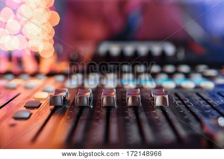 Top view od adjusters and red buttons of a mixing console. It is used for audio signals modifications to achieve the desired output. Applied in recording studios, broadcasting, television