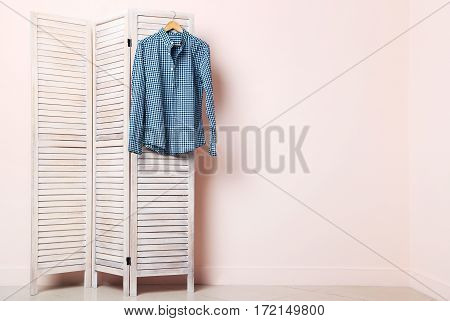 Male Shirt Hanging On Folding Screen On A Beige Background