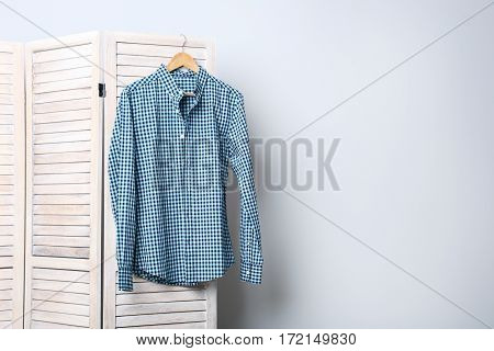 Male Shirt Hanging On Folding Screen On A Grey Background