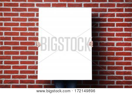 Man Holding Blank Poster On Brick Wall Background