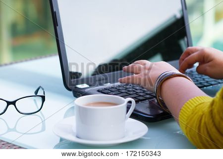 Hands Of Woman On The Keyboard Of Her Laptop Computer. Female Working On Laptop In A Street Cafe