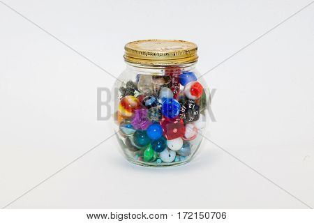 a jar containing dice, marbles and more