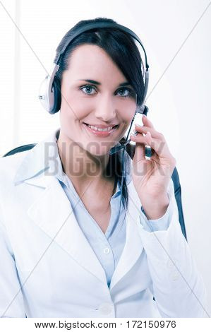 Female call center service operator at work. Attractive female helpdesk employee with headset at workplace. Business information help and support concept. Toned image