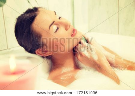 Young beautiful naked red-haired woman takes bubble bath. Concept of care of body. Toned image