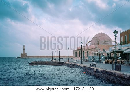 Venetian quay of Chania with Lighthouse and Kucuk Hasan Pasha Mosque during cloudy morning blue hour, Crete, Greece