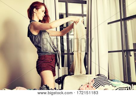 Attractive Red-haired Young Woman Packing A Travel Bag Before Go