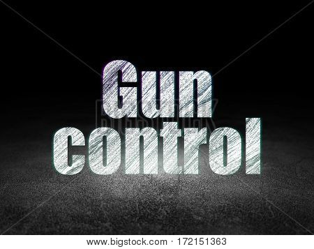 Privacy concept: Glowing text Gun Control in grunge dark room with Dirty Floor, black background